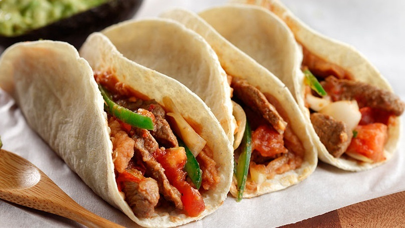 Three tortillas filled with steak, red and green peppers and salsa