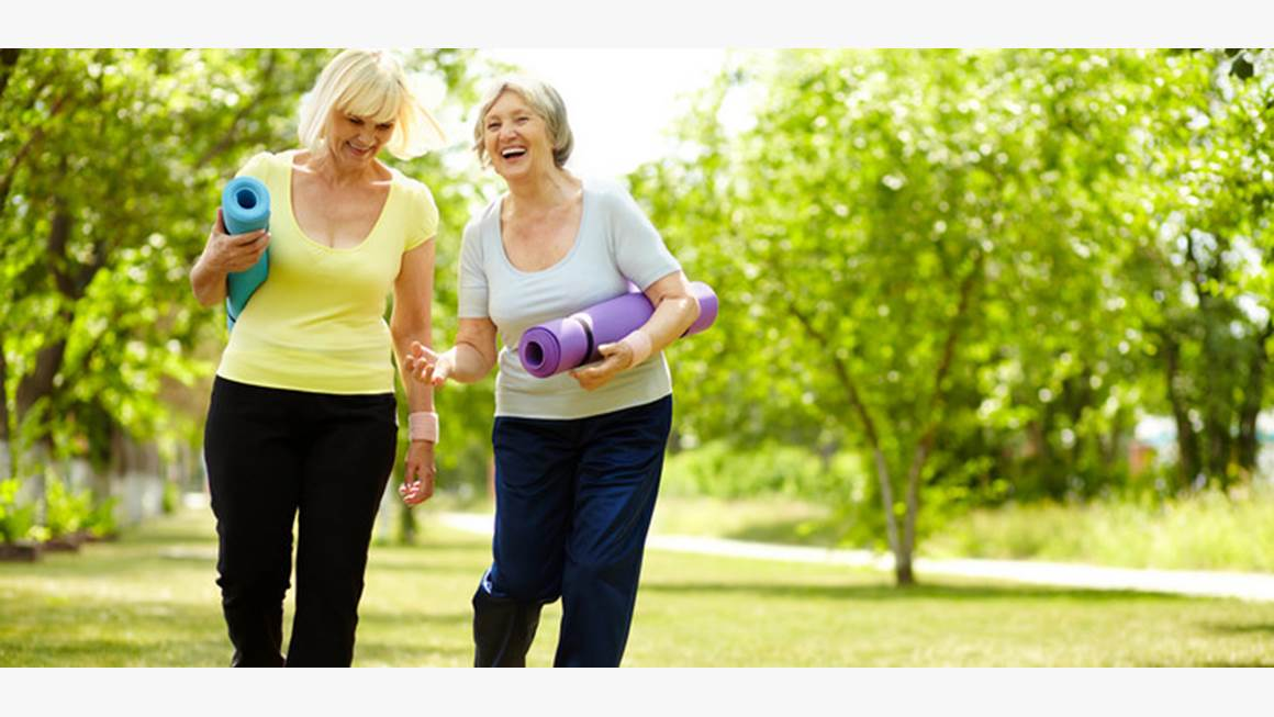 Two older women carrying yoga mats stroll through a park in the summertime, laughing.