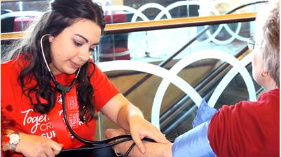 Young woman volunteer measuring an older woman's blood pressure