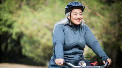 woman wearing helmet riding bicycle outdoors