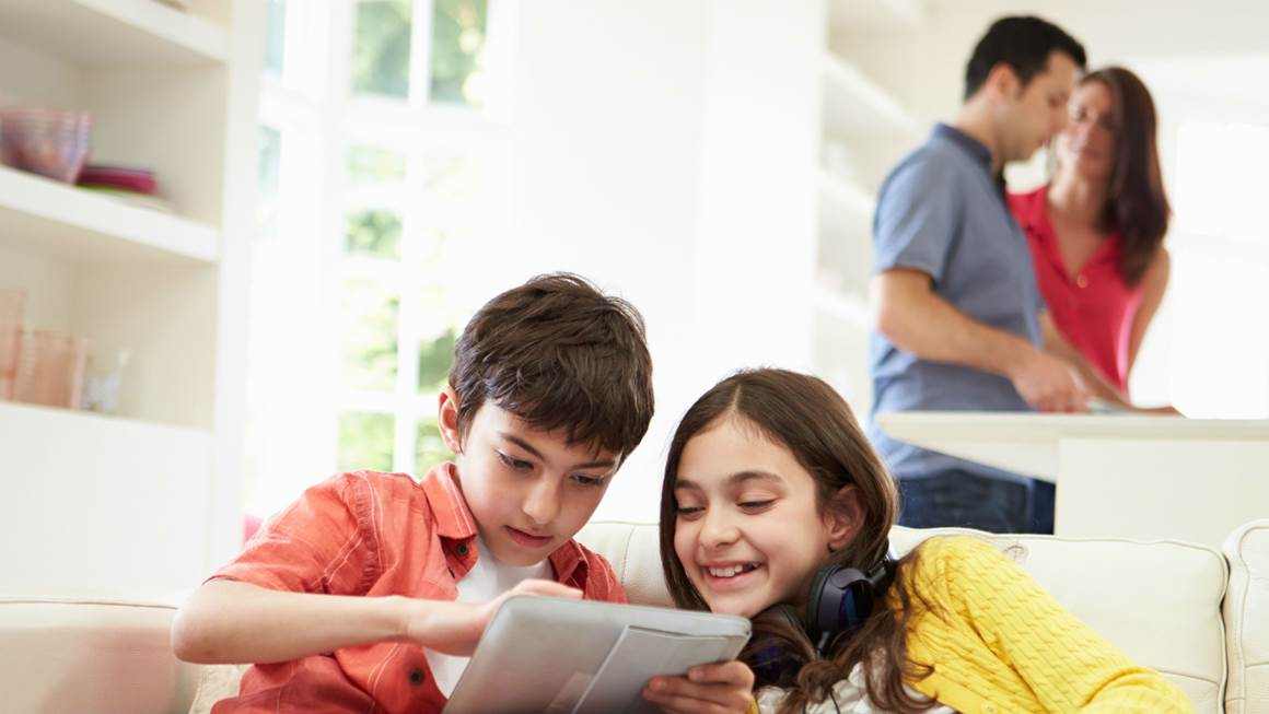 brother and sister playing on tablet while parents prepare dinner
