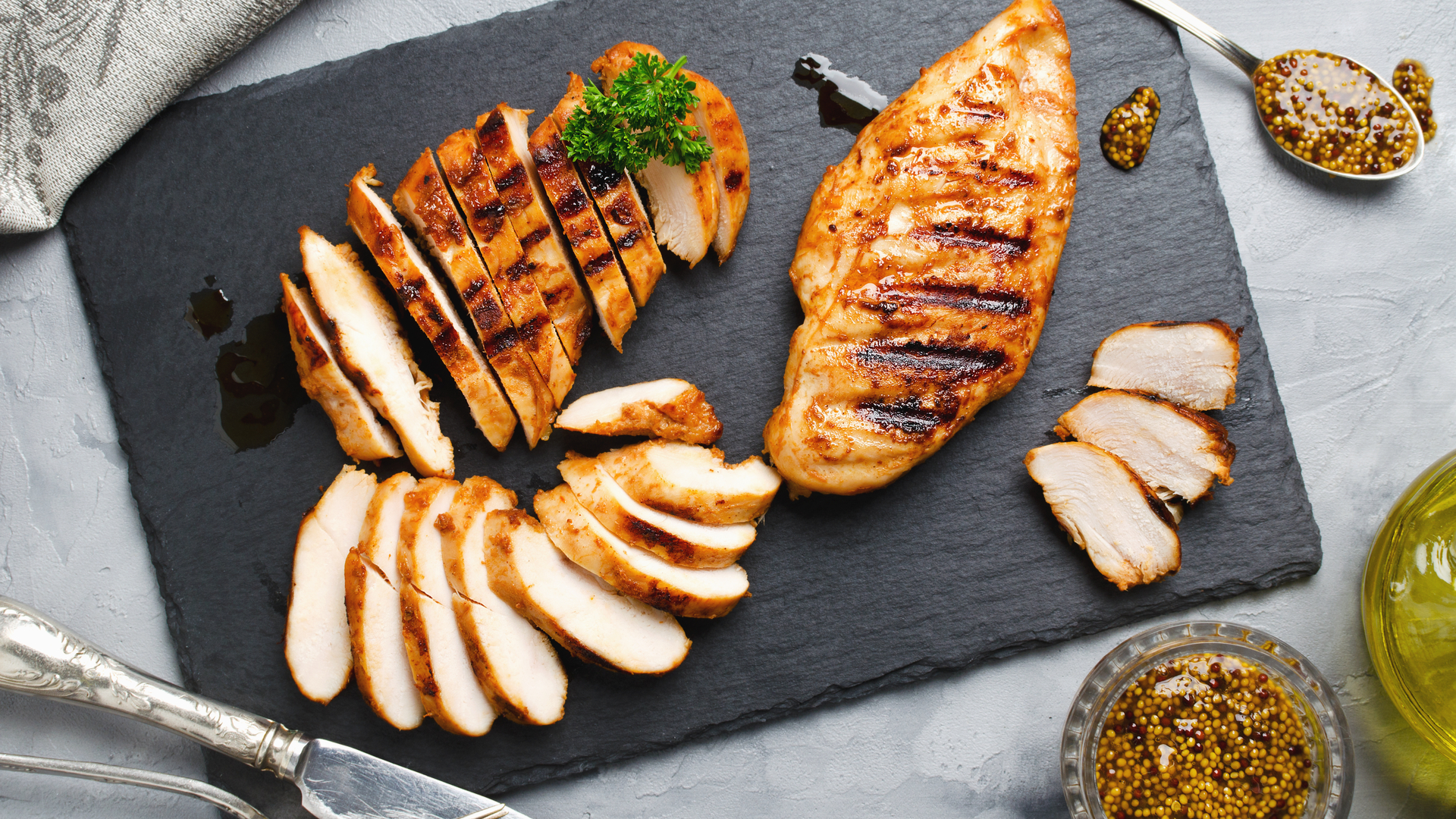 Grilled chicken cut into slices on a slate
