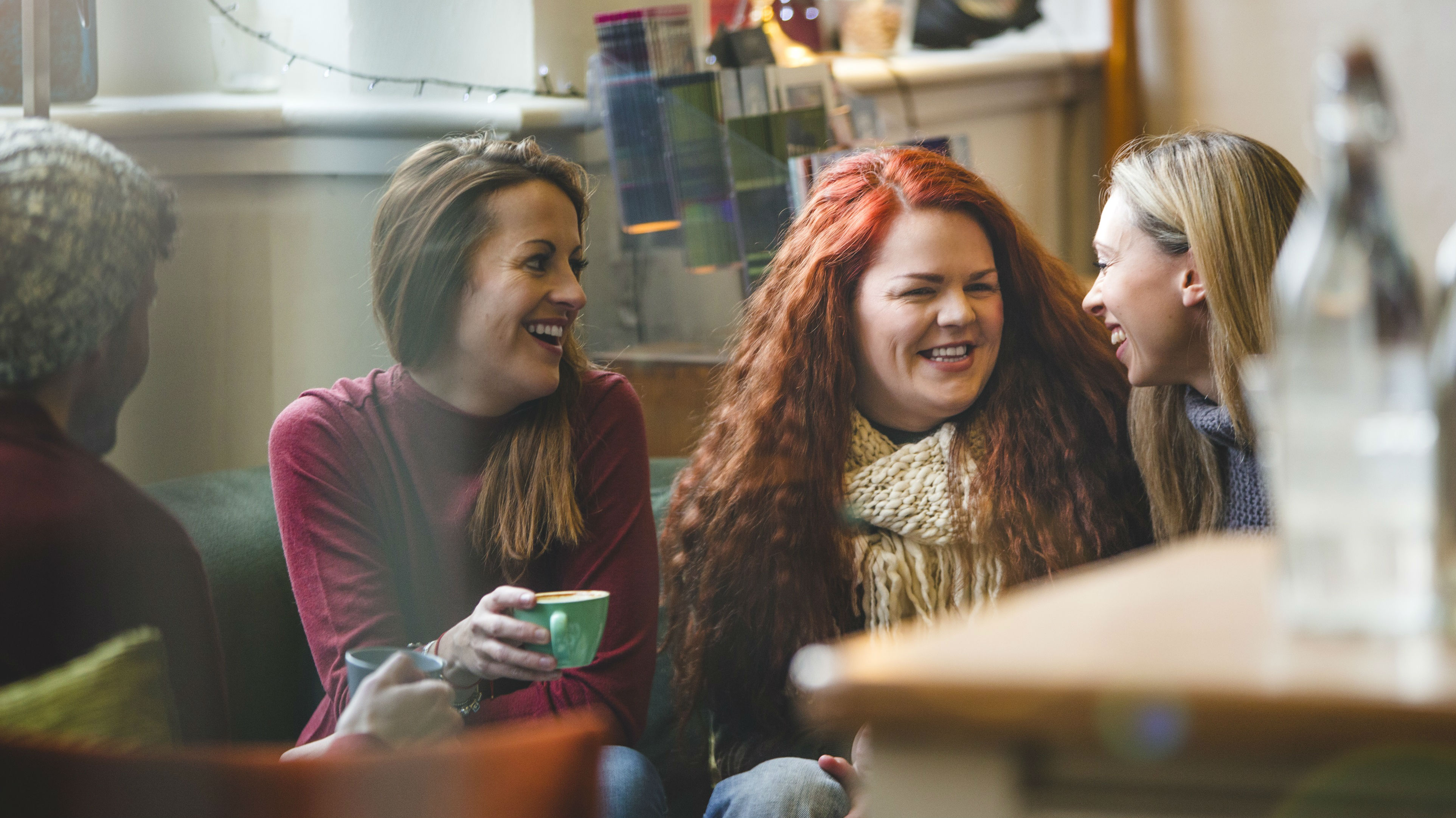 Group of female friends laughing at cafe