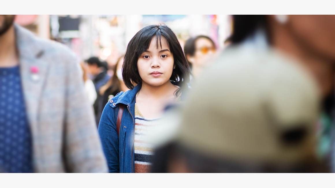 Girl in a crowd staring into the camera