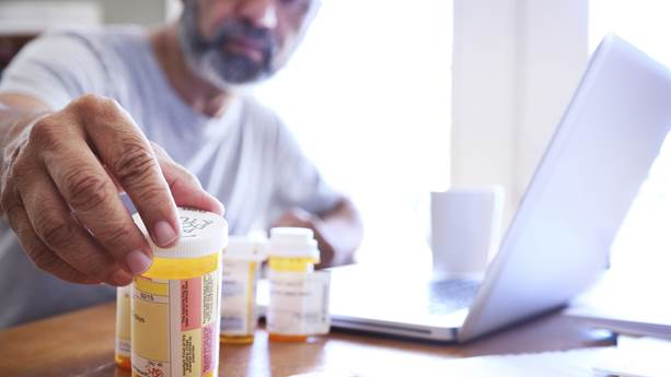 A man reaches for his prescriptions on a table.