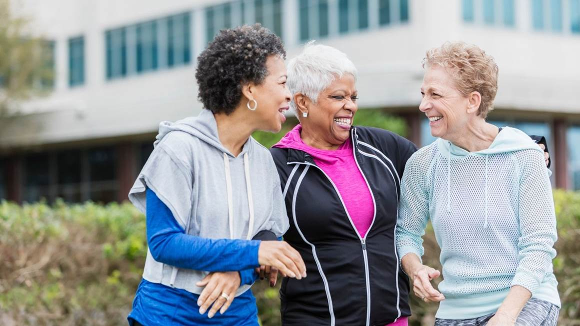 three women laughing in workout clothes.