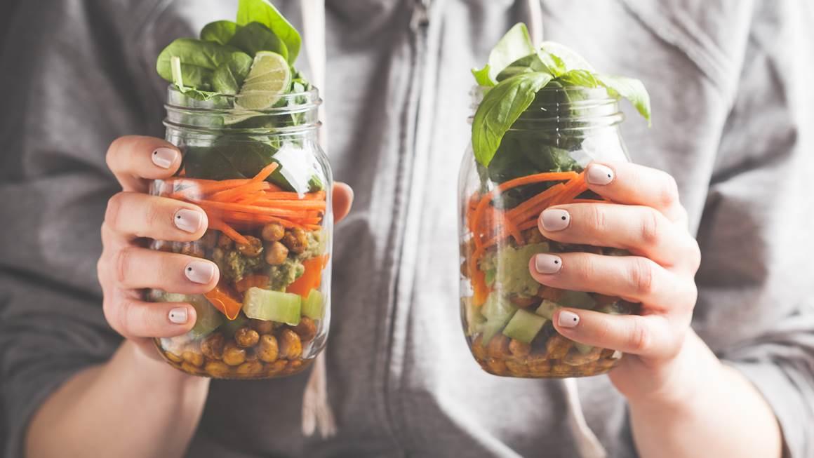Woman holding up salad jars