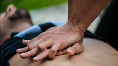 A man lies flat while someone does CPR on his bare chest