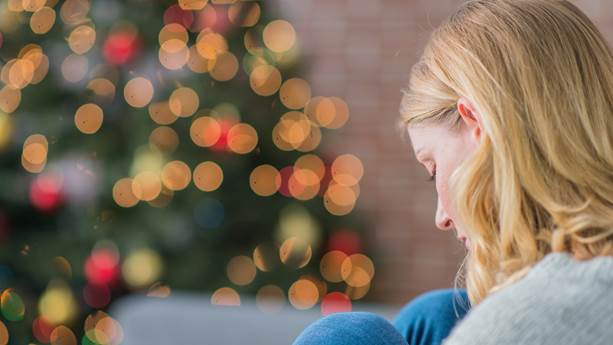 Woman sitting in front of a christmas tree looking sad