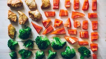 Chopped red pepper broccoli chicken on cutting board