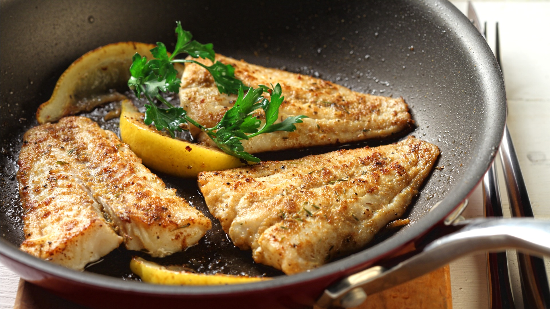 Three pieces of cooked fish in pan with lemon and herbs