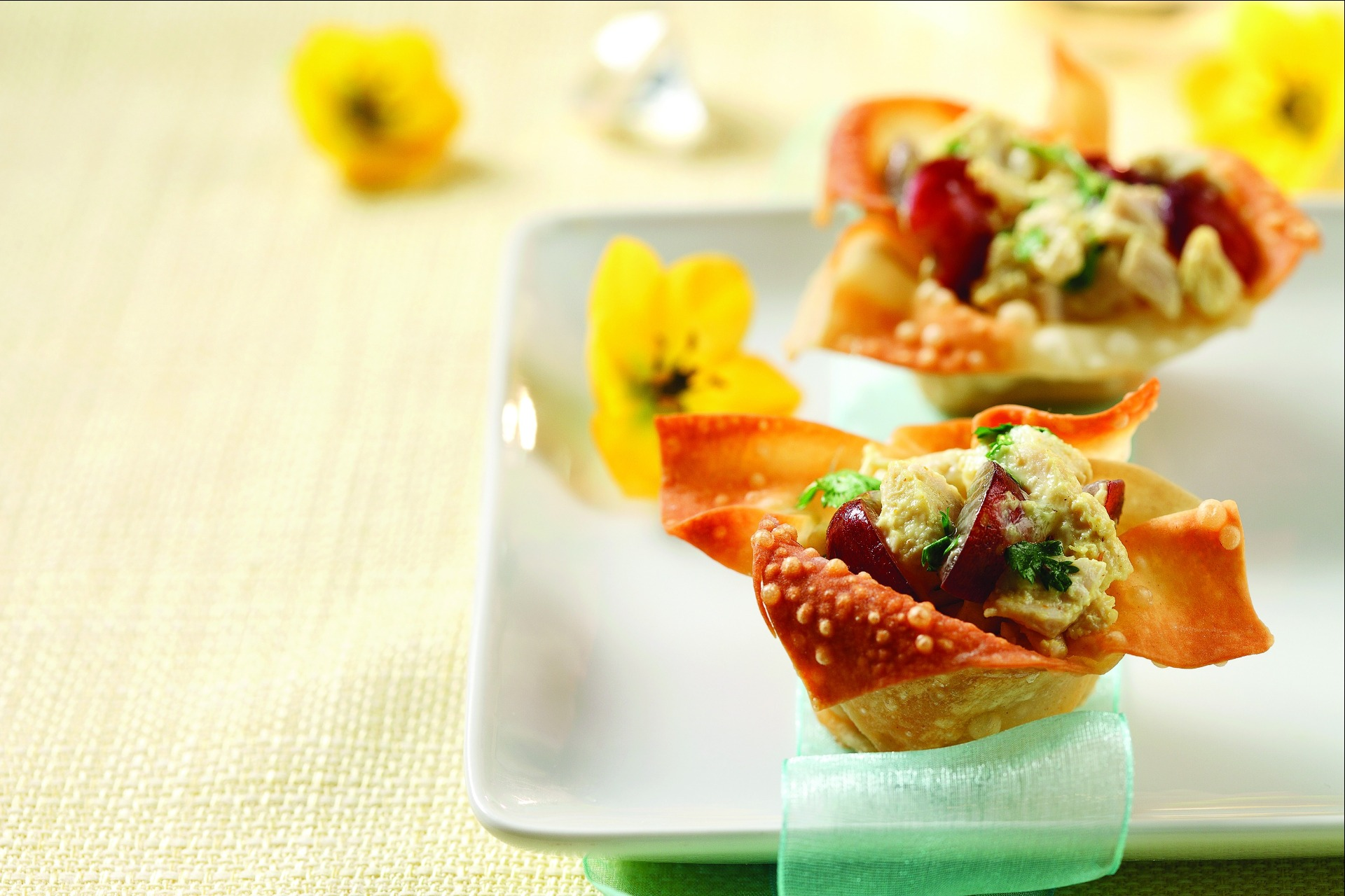 Curried chicken salad in wonton cups sitting on white plate with yellow flowers