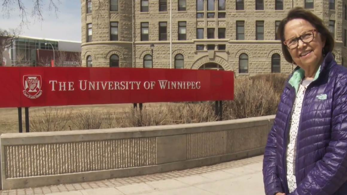 Esther Sanderson wears a purple jacket and smiles beside a University of Winnipeg sign.