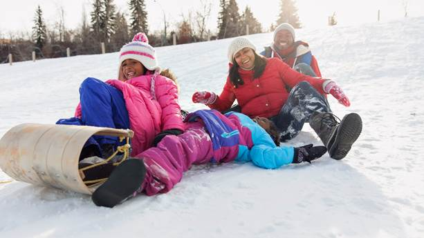 Family laughing as they toboggan down a snow-covered hill