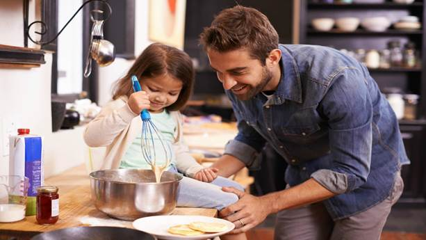 Father and daughter making pancakes in the kitchen