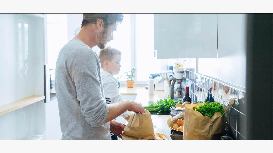 Father and son unpacking groceries in kitchen
