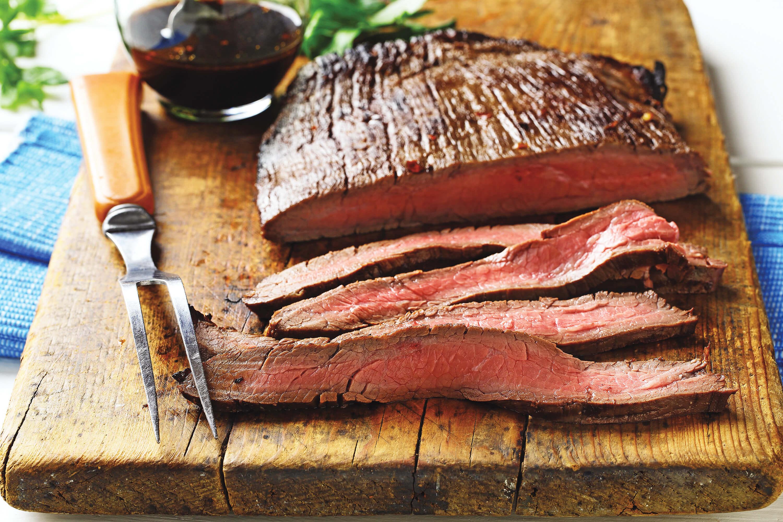 Sliced flank steak on wooden cutting board