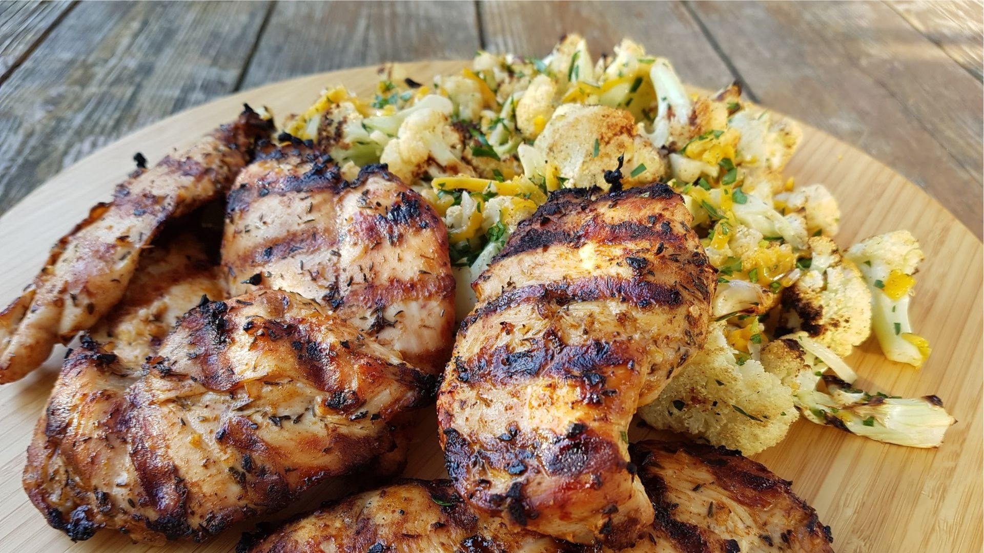 Grilled chicken breasts and cauliflower on wooden board