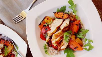 Sliced grilled chicken on barley, arugula, sweet potatoes and red peppers