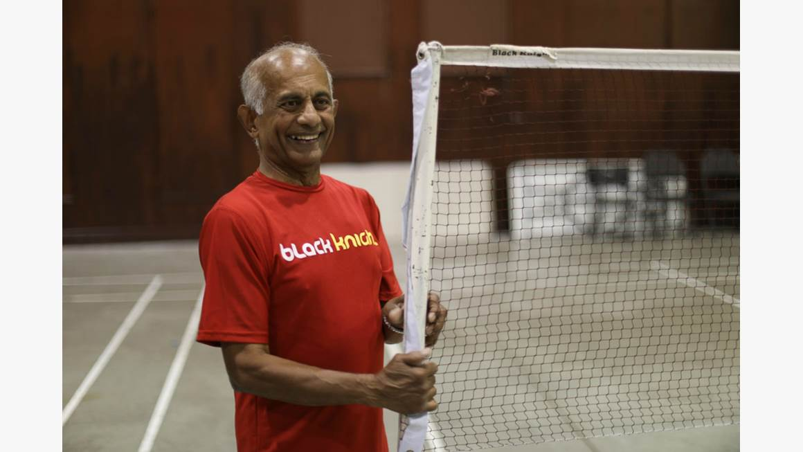 Jerry Alfonso wears a read T-shirt as he stands beside a badminton net in a gymnasium.