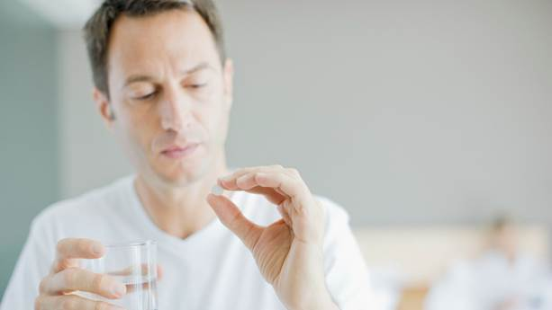 Man holding glass of water and an aspirin tablet