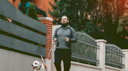 Man jogging outside with his dog