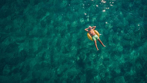 Man laying back on swimming ring in the sea