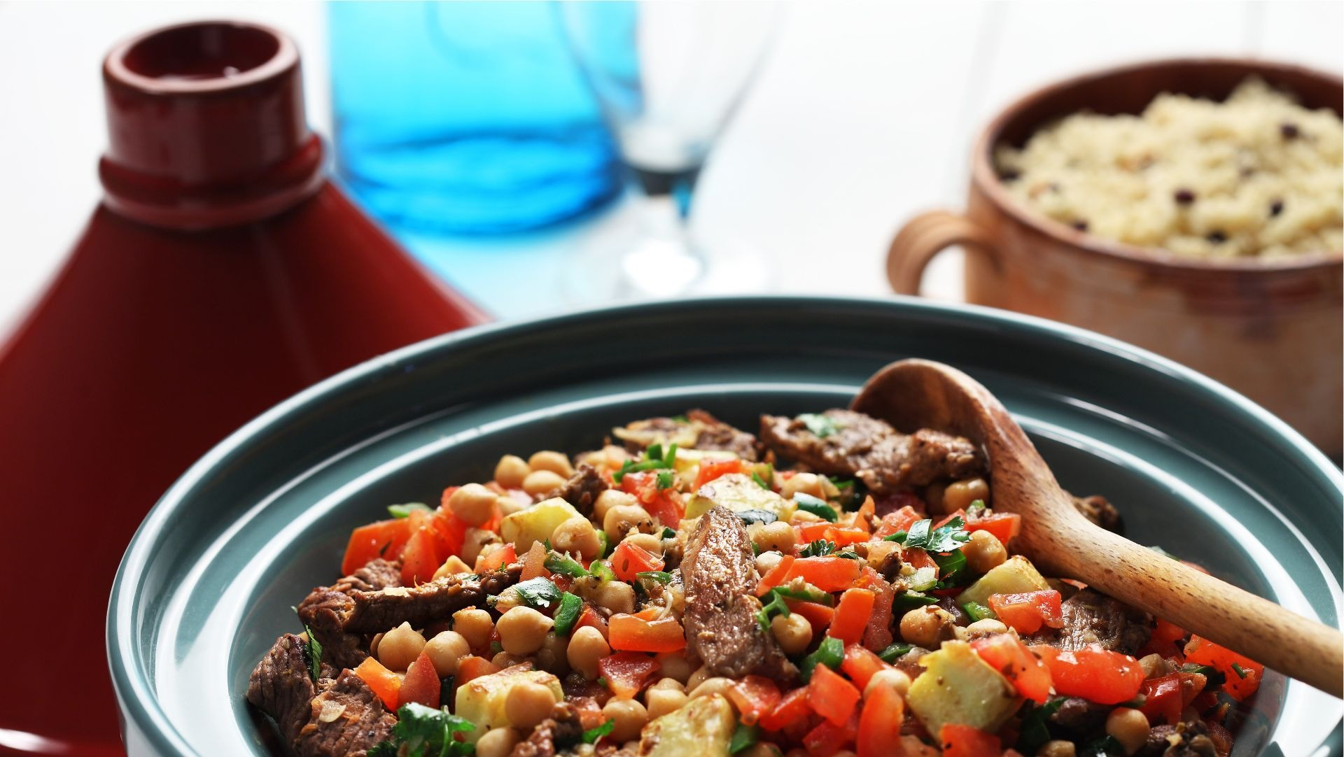 Bowl filled with chickpeas, lamb, chopped tomato, couscous and parsley