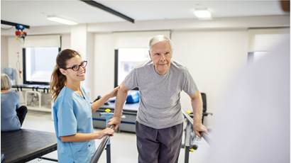Nurse guiding patient to walk on slope in rehab