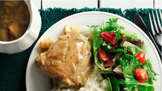 Plate with cajun garlic chicken thigh, mashed potato and salad