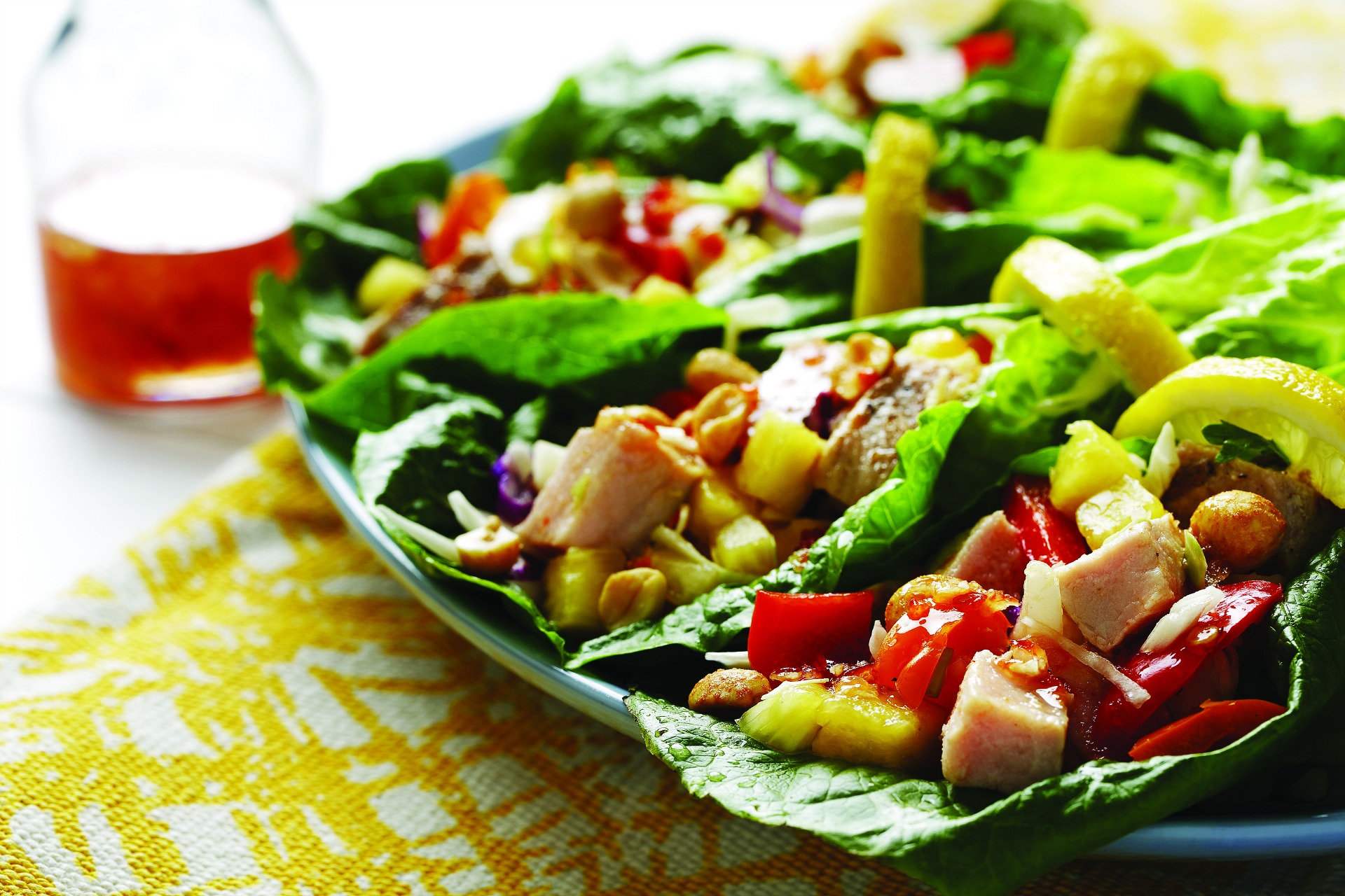 Chopped chicken, roasted red peppers, chopped pineapple and peanuts on a lettuce leaf