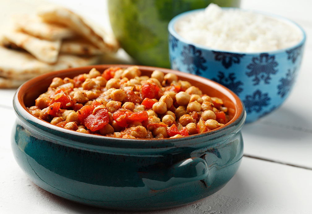 Cooked chickpeas, tomatoes in ceramic pot. Bowl of white rice and pita in background