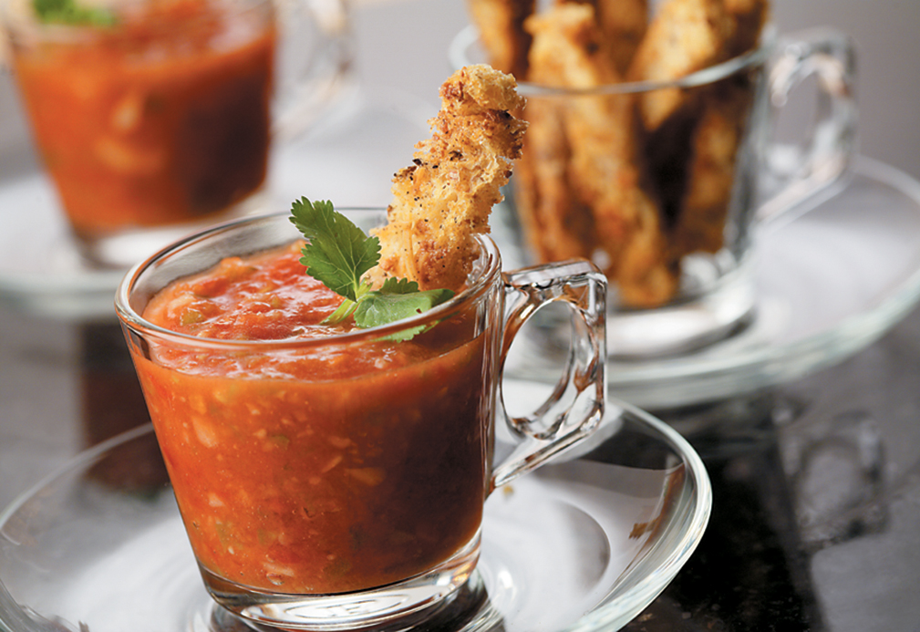 Gazpacho with multigrain croutons in a glass mug.