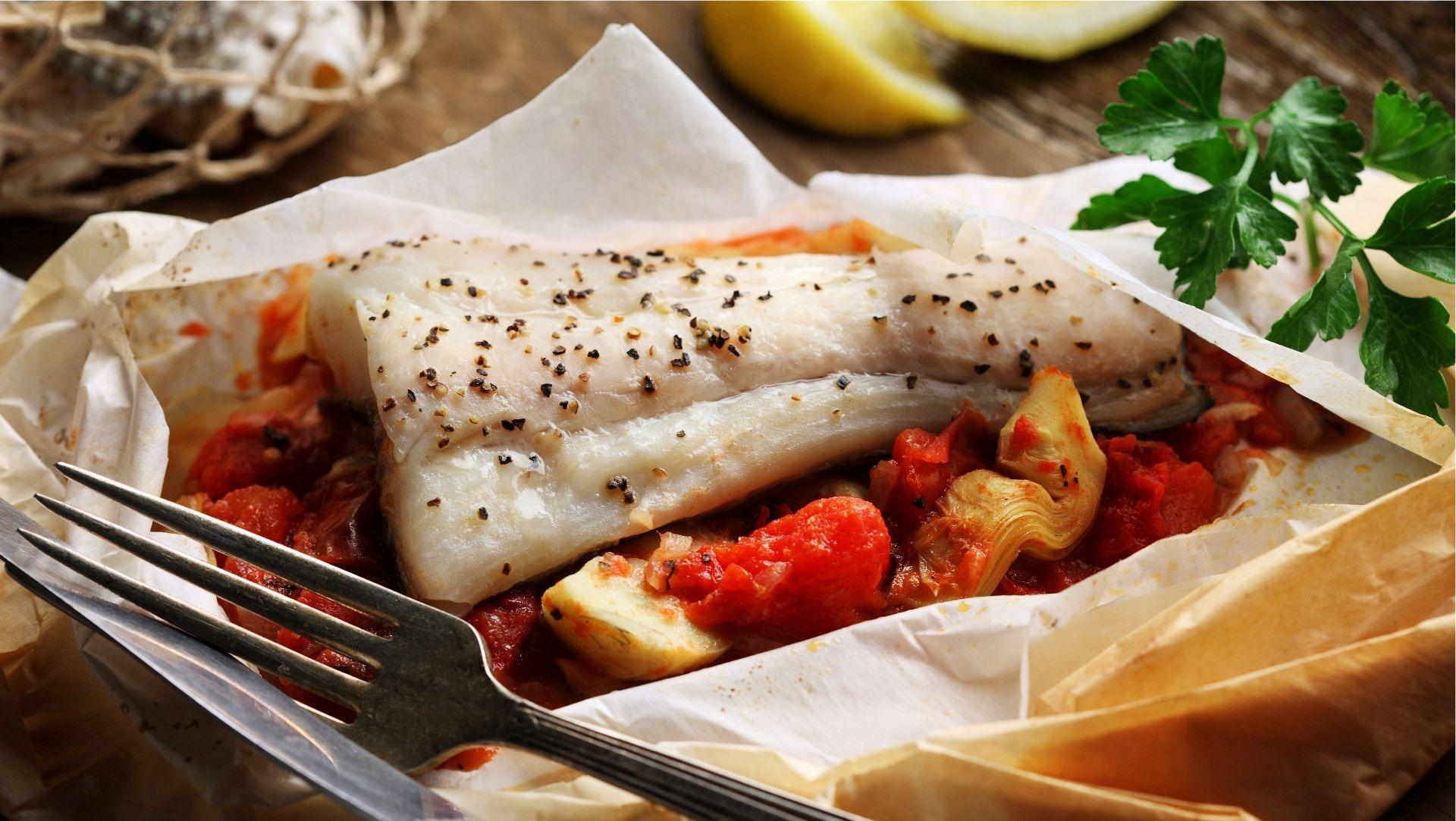Halibut filet with roasted tomato and artichoke in wax paper packet