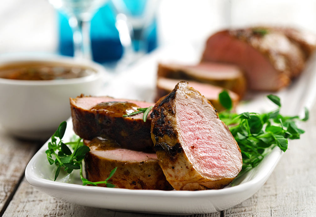 Sliced pork tenderloin with maple sauce on plate with greens