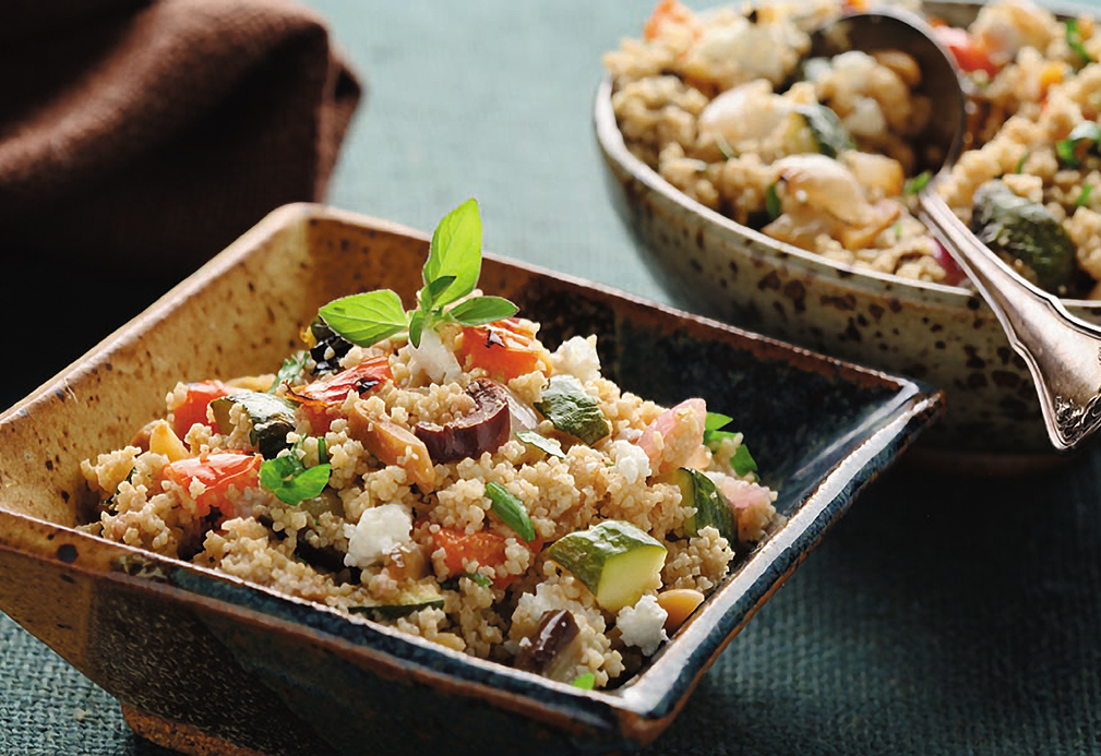Mediterranean salad with roasted vegetables and whole wheat couscous in a square bowl.