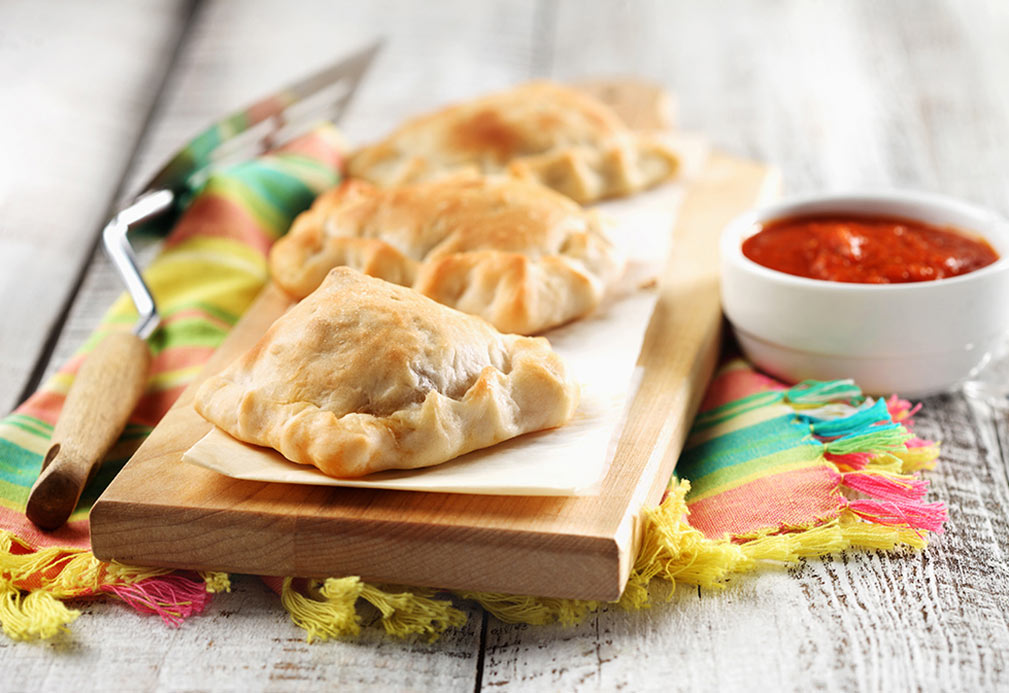Three mini calzones on wooden cutting board with bowl of marinara dipping sauce.