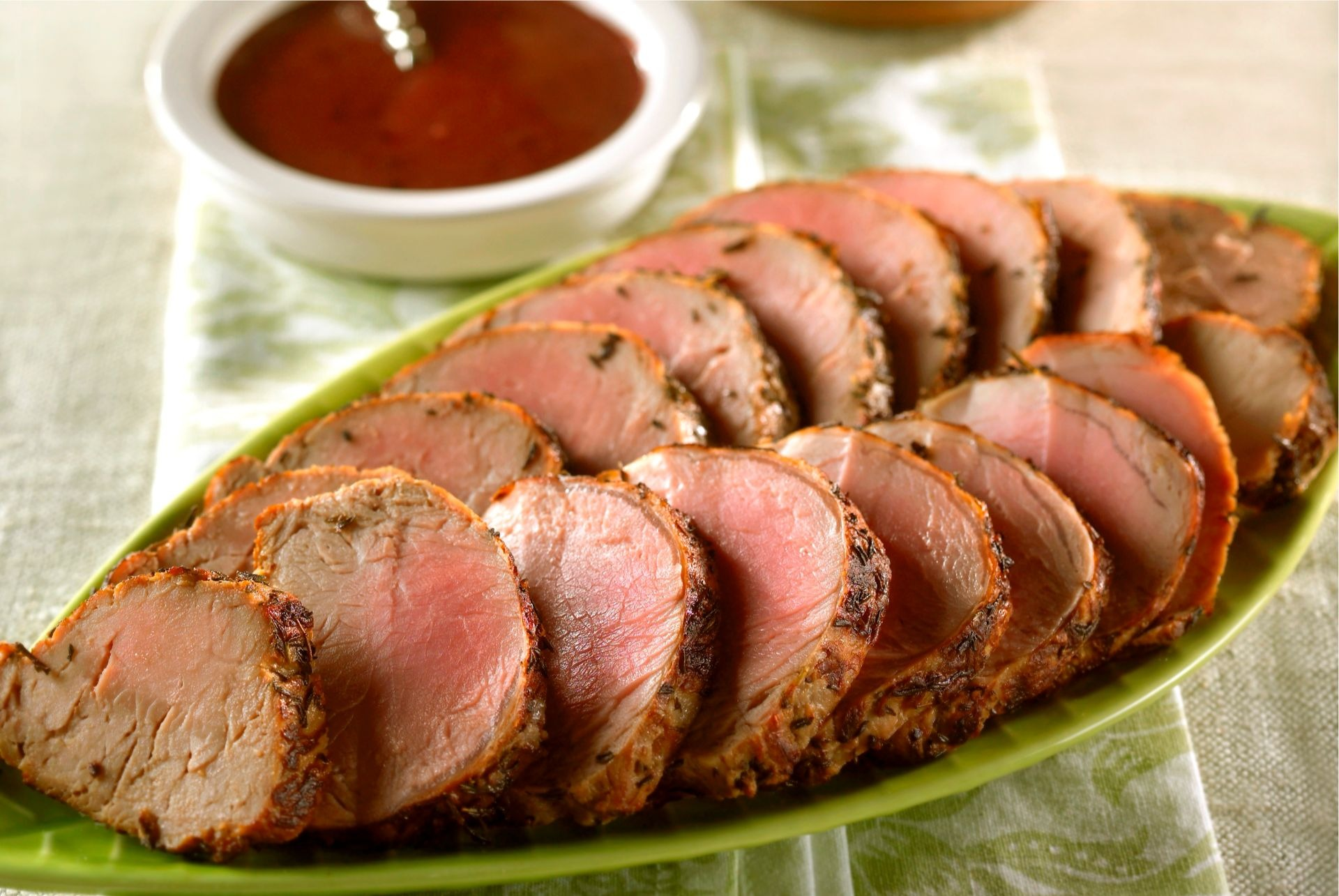 Platter of sliced pork tenderloin with small dish of raspberry mustard sauce in background