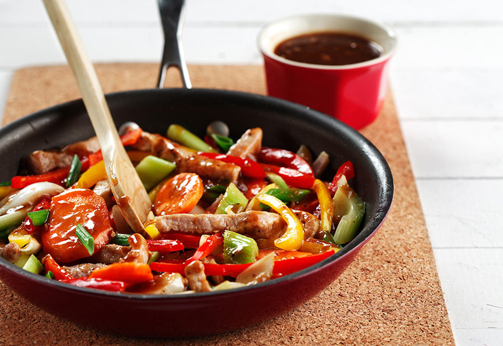 Skillet with sliced pork, peppers, celery, carry and black bean sauce