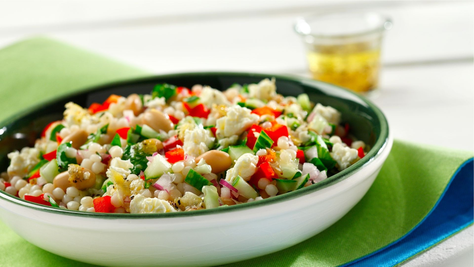 Rosemary-feta pearl couscous salad in a white bowl on a green placemat.