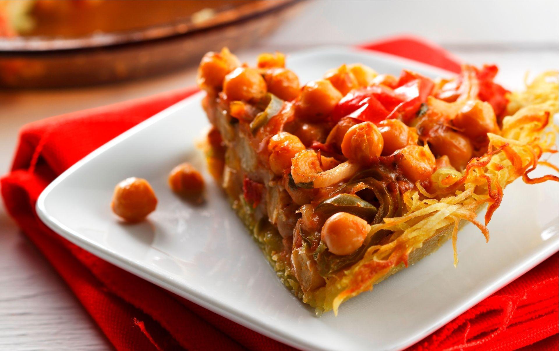 Slice of garbanzo bean pie with potato crust on white plate
