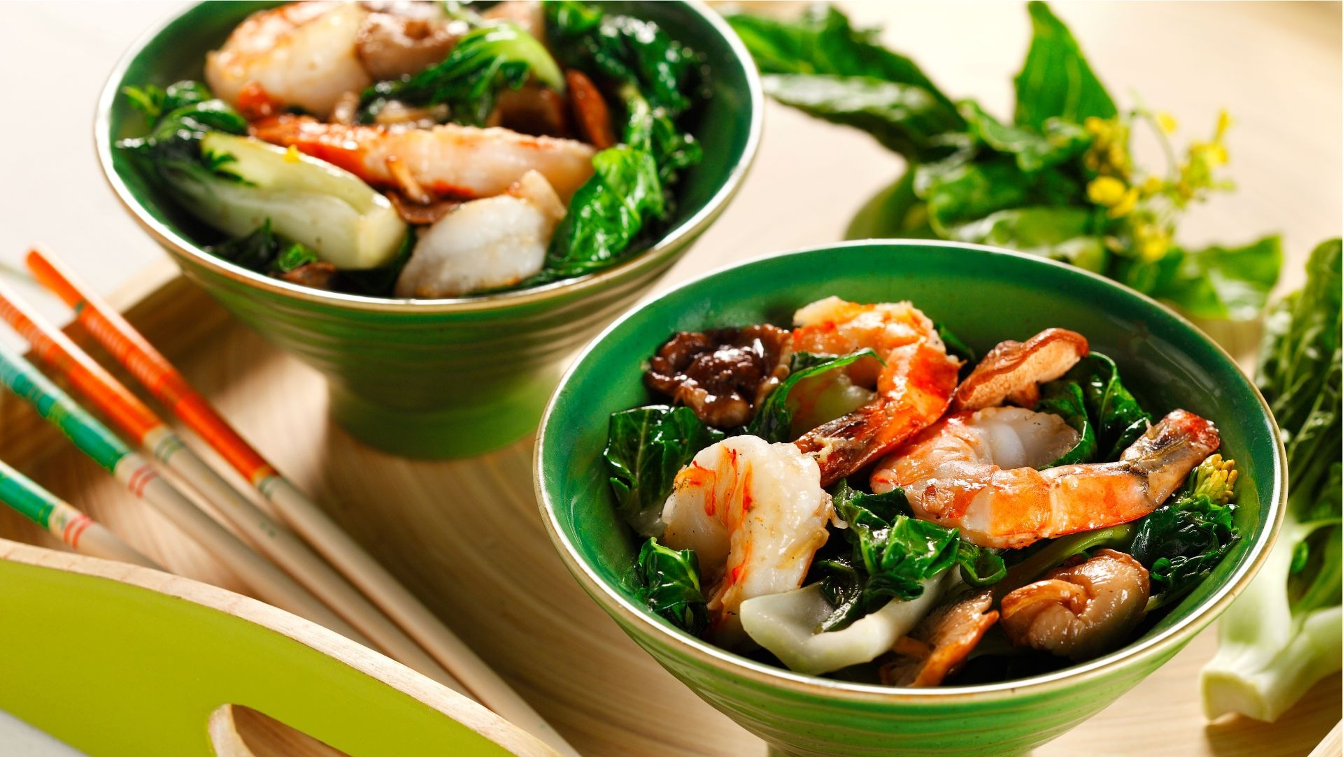 Two bowls filled with shrimp, mushrooms and bok choy on wooden serving tray with chop sticks