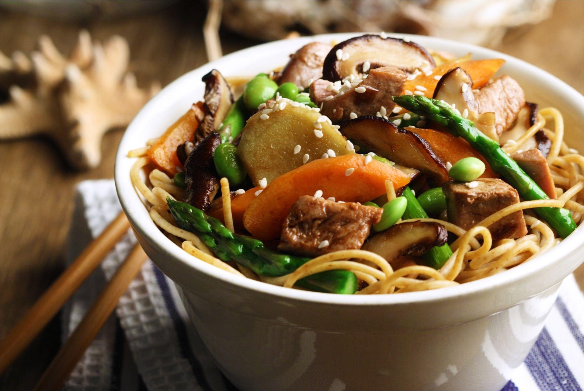 Bowl of vermicelli noodles, edamame, shiitake mushrooms, tuna steak, carrot and asparagus spears