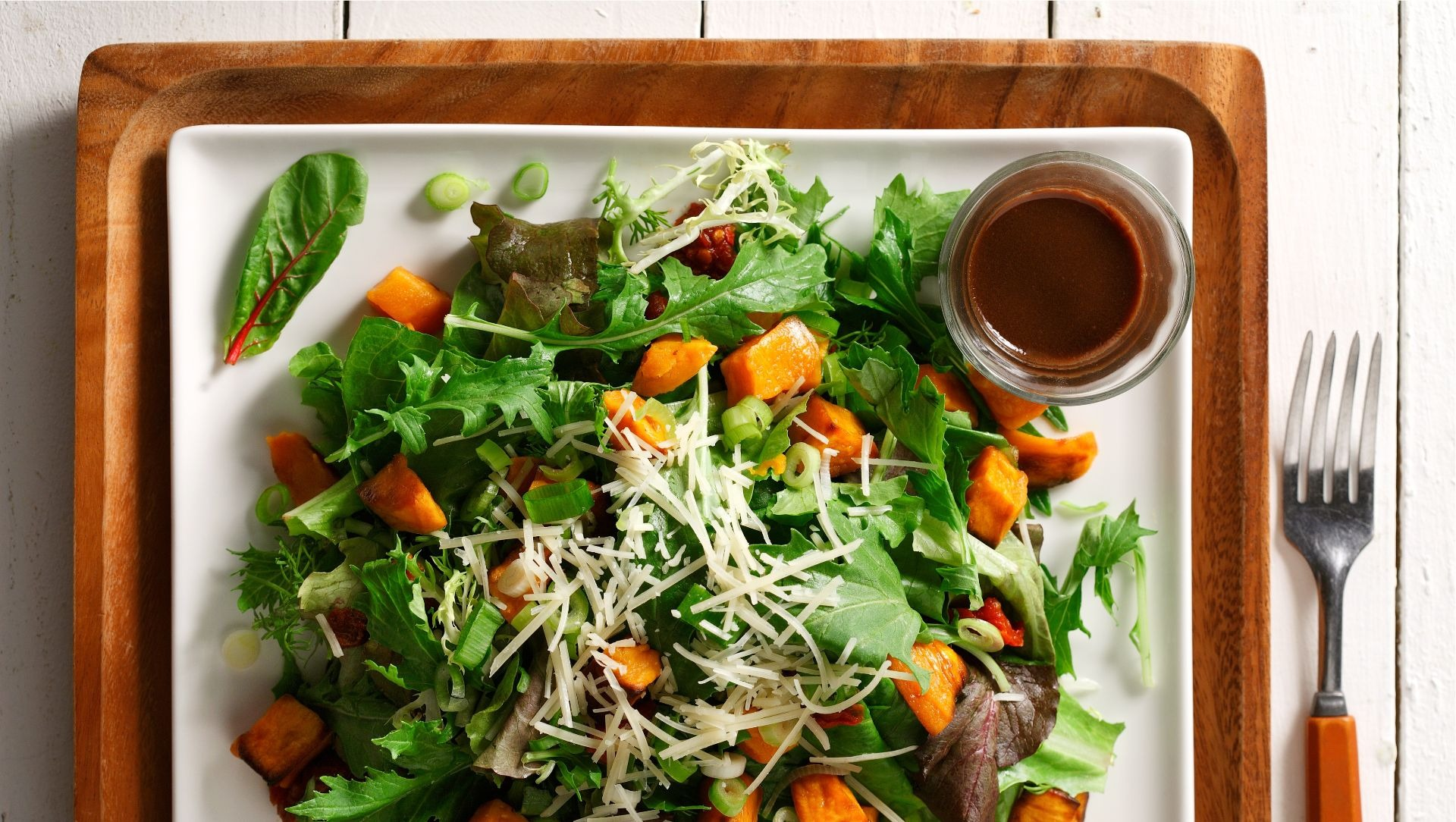 Warm sweet potato, sundried tomato and arugula salad on a white square plate.