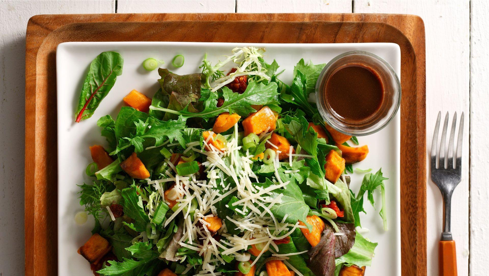 Warm sweet potato, sundried tomato and arugula salad on a white square plate.