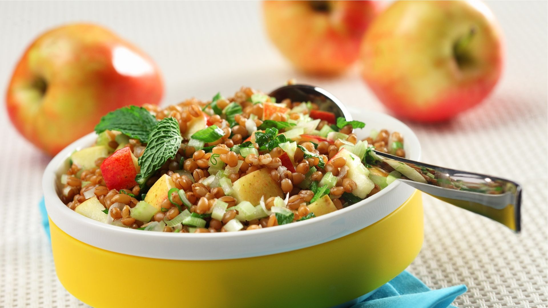 Wheat berry and apple salad in a yellow bowl on a blue napkin.