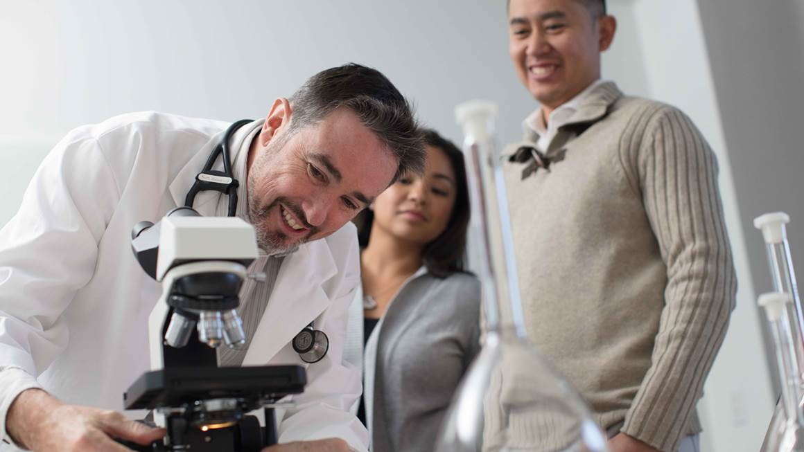 Dr. Kim Connelly leans over a microscope while two people look on.