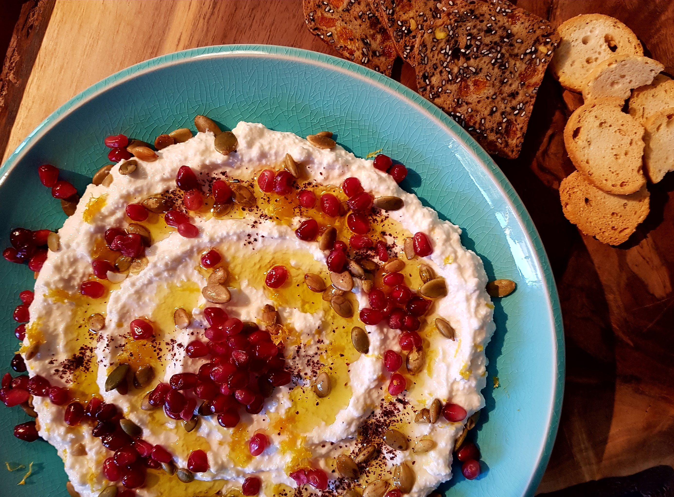 Ricotta and yogurt spread topped with pomegranate, pumpkin seeds and olive oil