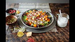 Roasted squash, lentils, arugula, pumpkin seeds, pomagranate salad in bowl