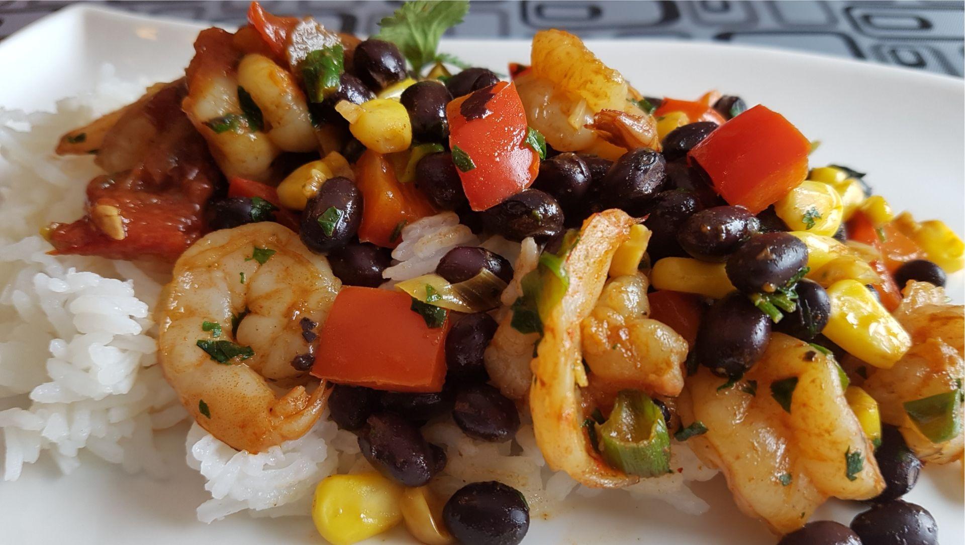 Shrimp, red peppers, black beans, corn, white rice on plate